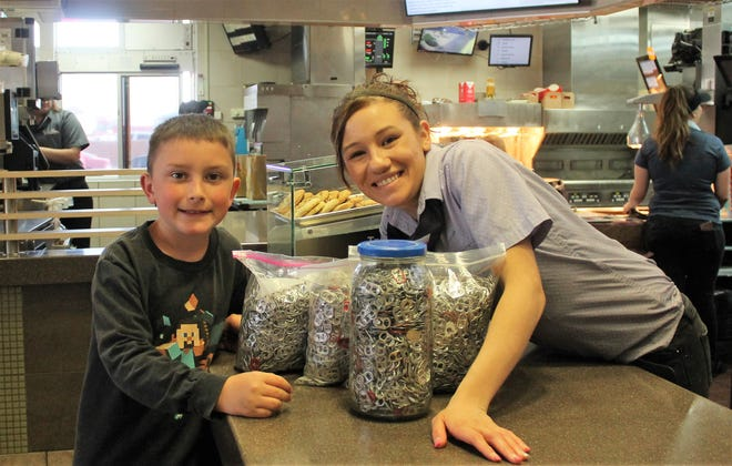 High Rolls Mountain Park third grader Brayden Berger, left, presents eight pounds of can tabs to Alamogordo McDonald's Department Manager Anna Martin Wednesday.  The donation is going to benefit Ronald McDonald House.