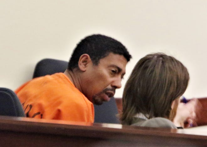 Fernando Azofeifa whispers to his attorney Thursday during a District Court hearing  in Aztec.