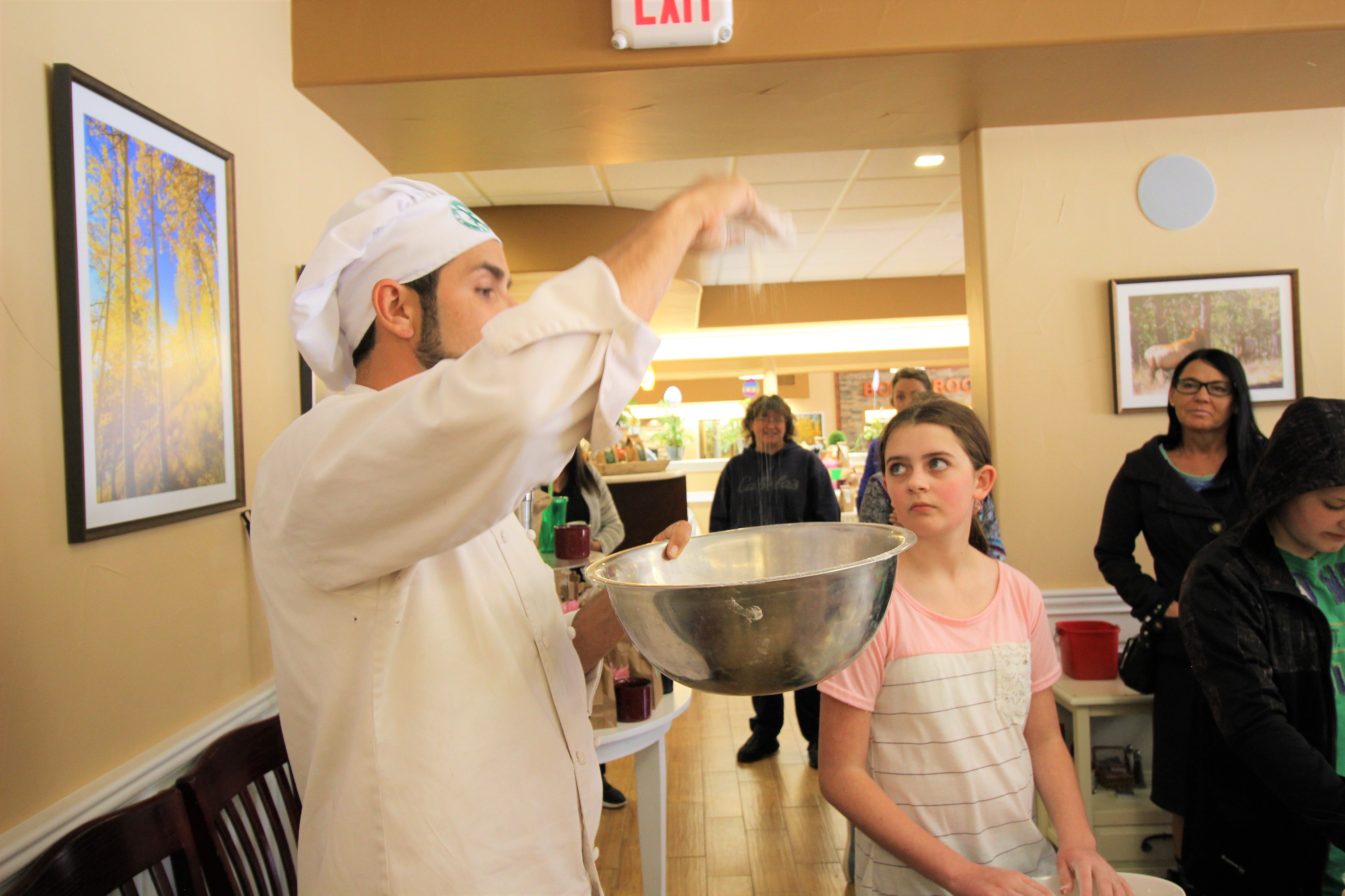 Steve Gomez shows children how to blend butter and flour using a traditional method, keeping the ingredients from becoming too warm, which will ruin the dough.