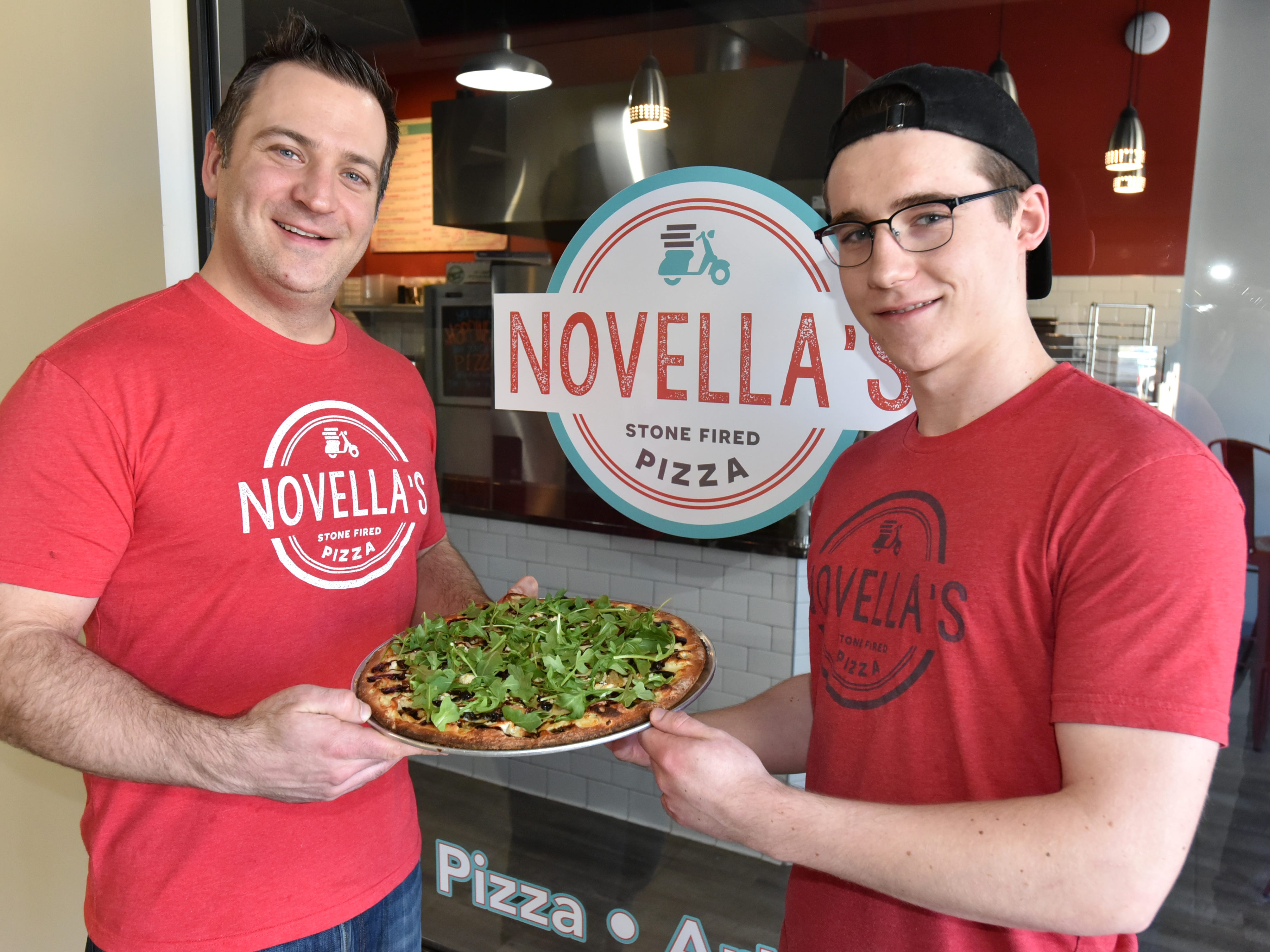 Brandon Davis and Novella's employee Joe Ellis, right, hold a finished example of their Fig & Pig pizza at their New Hudson pizzeria.