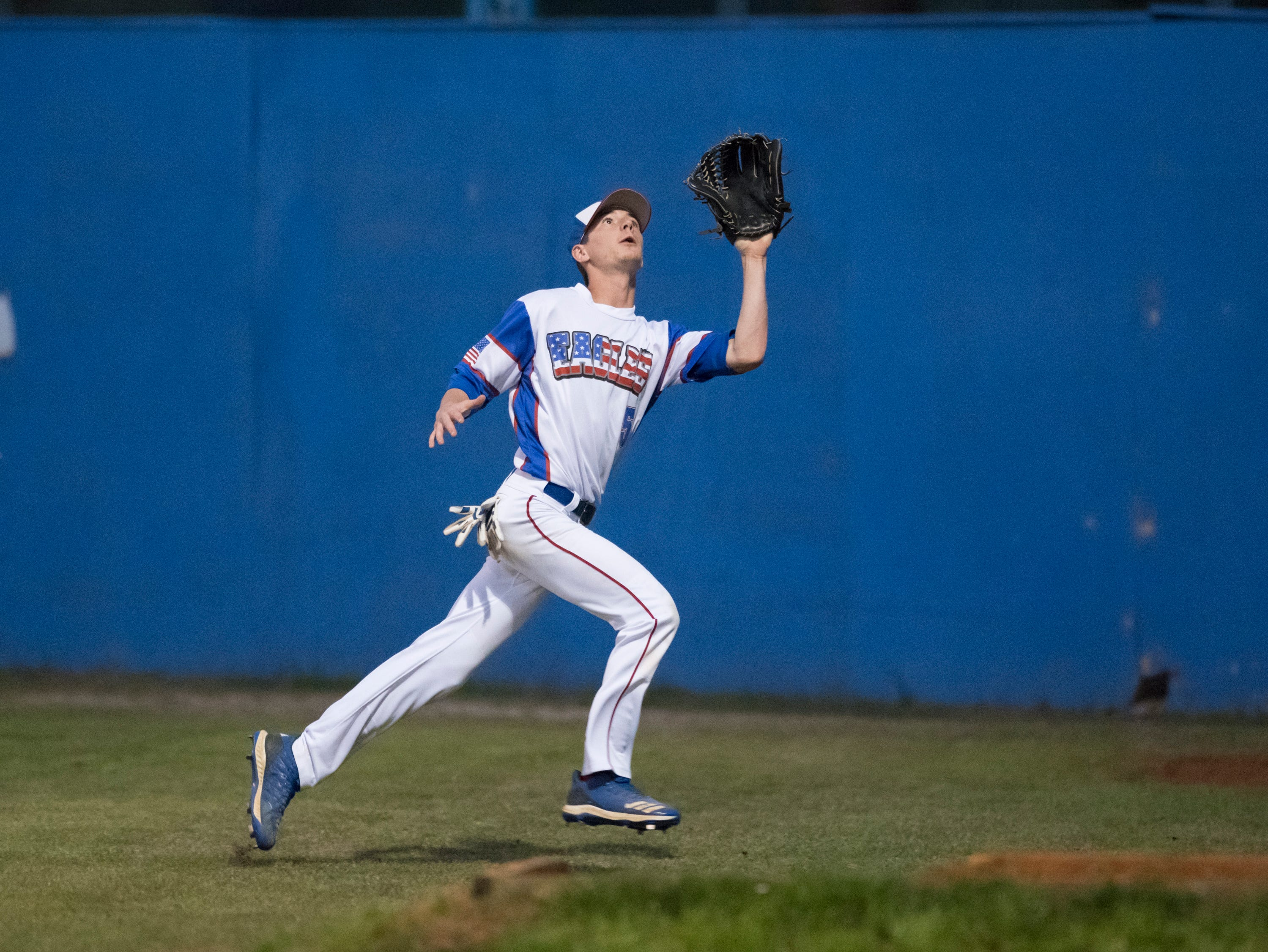Right fielder Chase Gullatt (5) makes a running catch before running into the fence during the Christian Educational Consortium vs Pine Forest baseball game at Pine Forest High School in Pensacola on Wednesday, April 3, 2019.