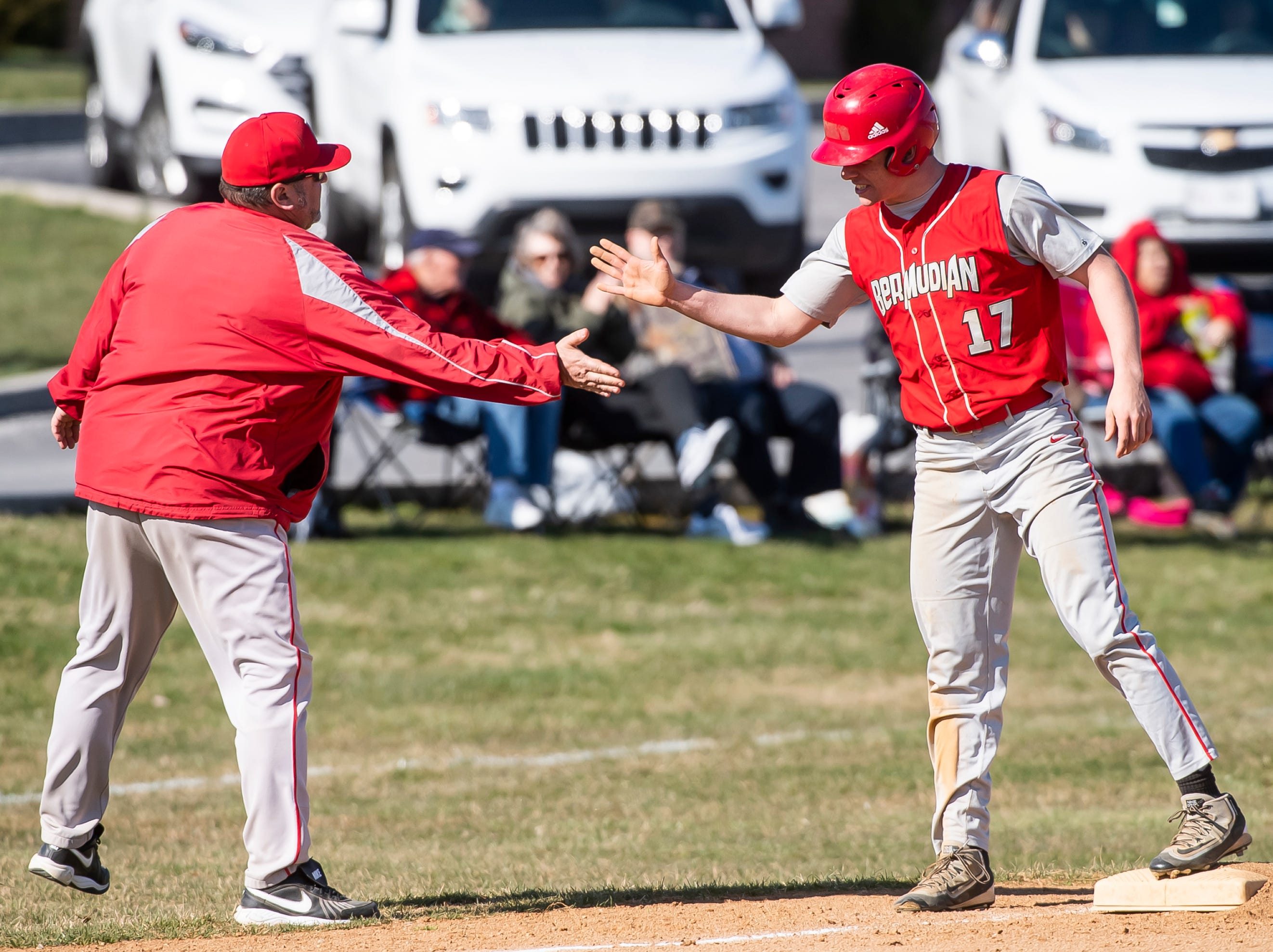 Bermudian Springs' Nate McCollum (17) gets a high-five from assistant coach Eric McClintic during a YAIAA baseball game against West York on Wednesday, April 3, 2019. The Eagles fell 14-11.