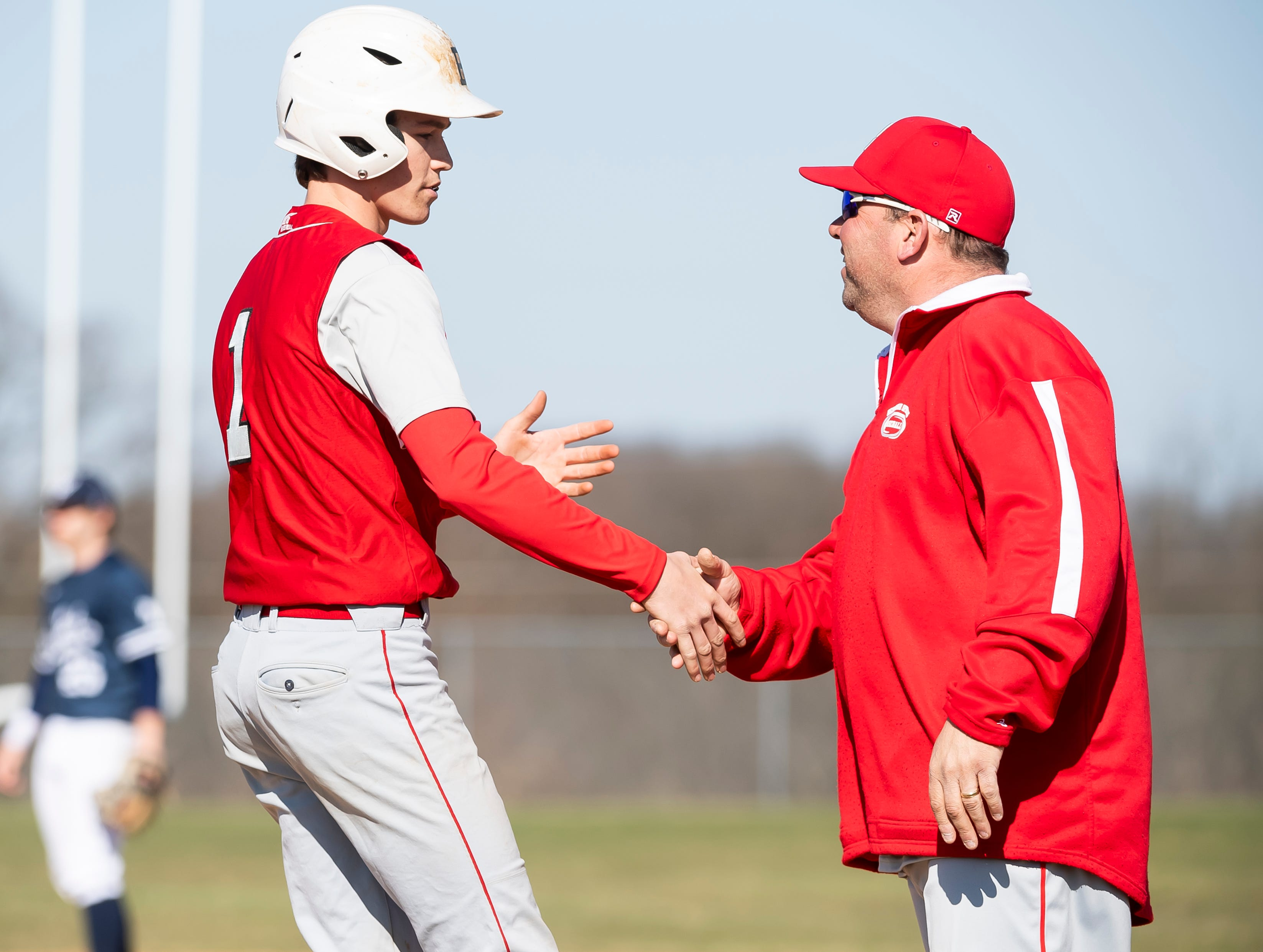 Bermudian Springs assistant coach Jeff Carpenter gives Tucker Byers (1) a handshake after Byers reached base during a YAIAA baseball game against West York on Wednesday, April 3, 2019. The Eagles fell 14-11.