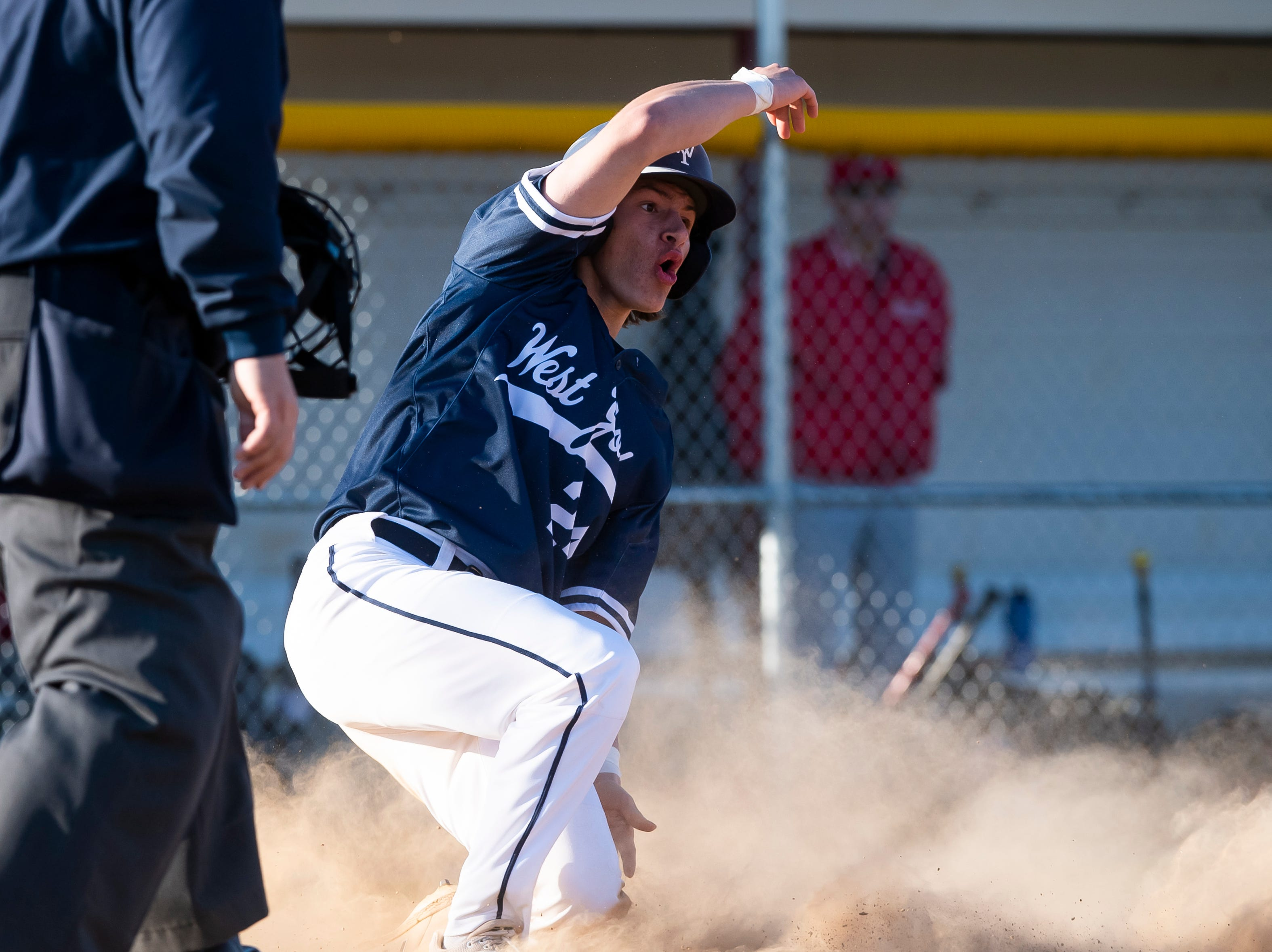 West York's Blaise Tanner reacts after sliding into home plate to score a run during a YAIAA baseball game against Bermudian Springs on Wednesday, April 3, 2019. The Bulldogs won 14-11.