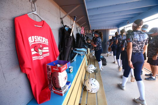 A Nebraska shirt hangs in the dugout to honor their former booster club president Dan Renyer, who died last December, during a Cactus High softball practice on Apr. 2, 2019 at Cactus High School in Glendale, Ariz.
