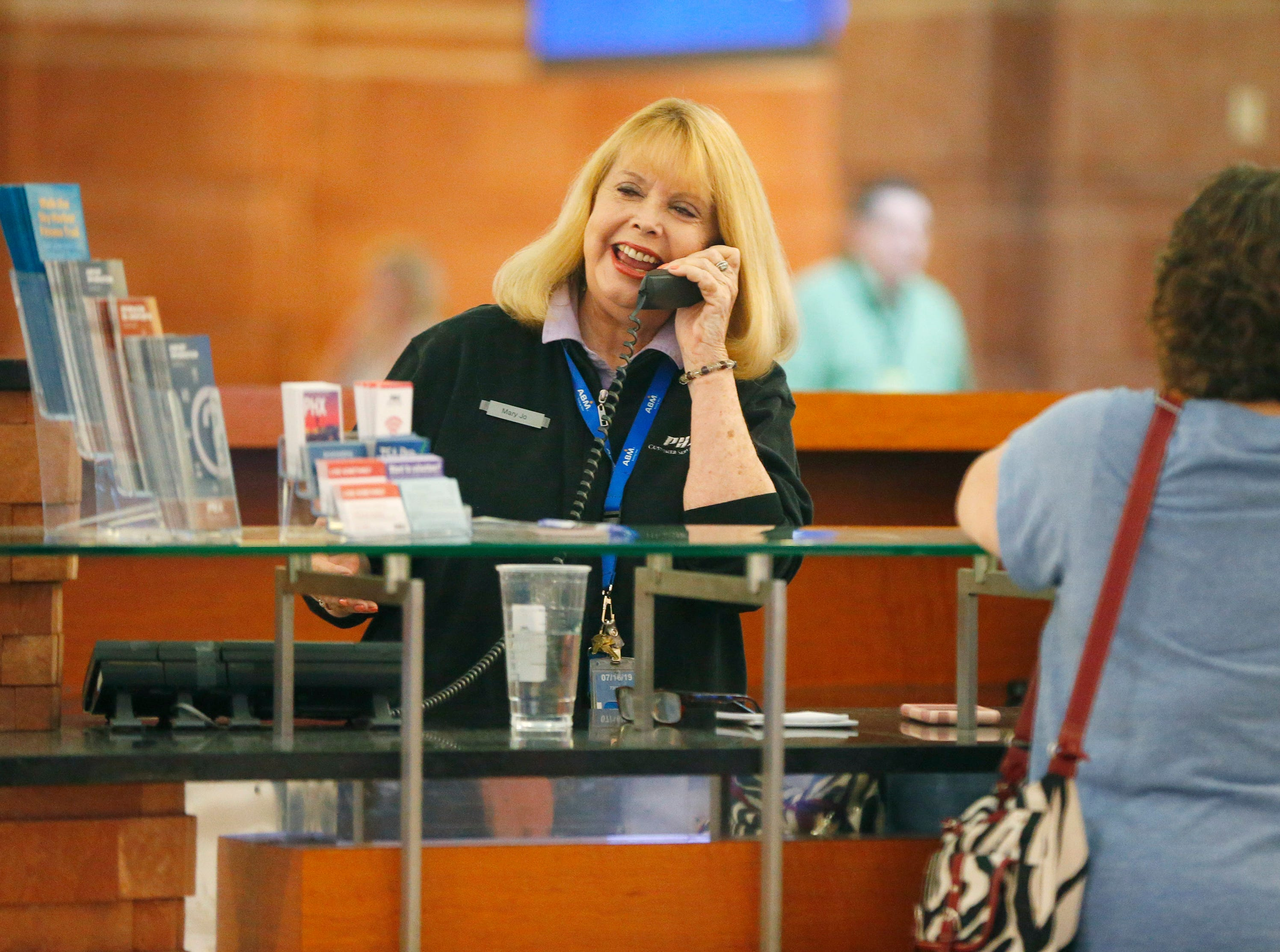 Mary Jo West helps Donna Rapp while working at the information desk at Phoenix Shy Harbor Airport on April 3, 2019. The first female news anchor in Arizona has been a volunteer at Terminal 4 for three months.