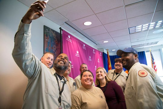 Mayor Kate Gallego (center) takes a selfie with city employees during the announcement of the city of Phoenix raising the minimum wage to $15 for all employees on April 4, 2019. From left, Stennis Robinson, Angie Perches, Mayor Kate Gallego, and Cymon Garrett.