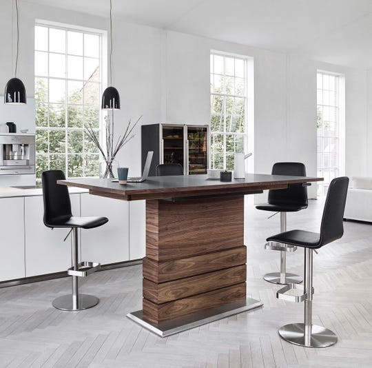 The Karsten high-rise dining table by Skovby of Denmark features rich walnut wood, self-storing extendable leaves, and cutting-edge motion technology, adjusting in height at the touch of a button to serve a range of home and entertaining functions.