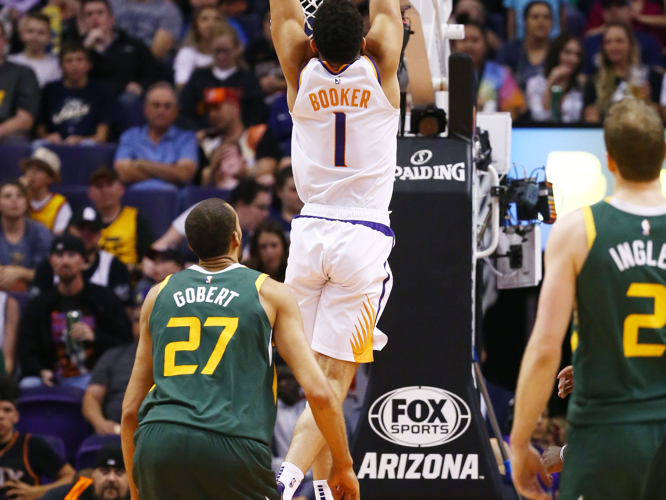 Phoenix Suns guard Devin Booker (1) slam dunks the ball past Utah Jazz center Rudy Gobert (27) in the first half on Apr. 3, 2019 at Talking Stick Resort Arena in Phoenix, Ariz.
