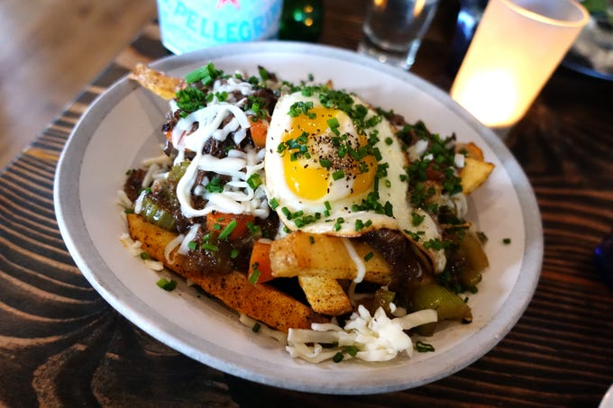 Short rib fries with demi-glace, mozzarella, chives, egg and roasted vegetables at Hidden Kitchen in Phoenix.