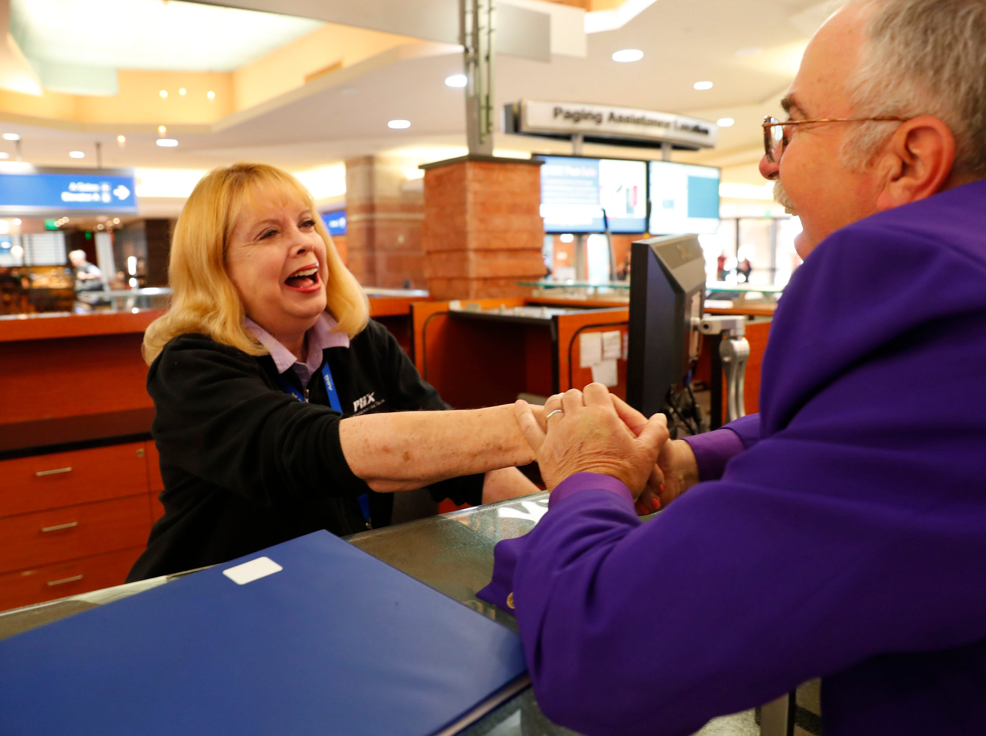 Mary Jo West shakes hands with John Vitt while working at the information desk at Phoenix Shy Harbor Airport on April 3, 2019. The first female news anchor in Arizona has been a volunteer at Terminal 4 for three months.