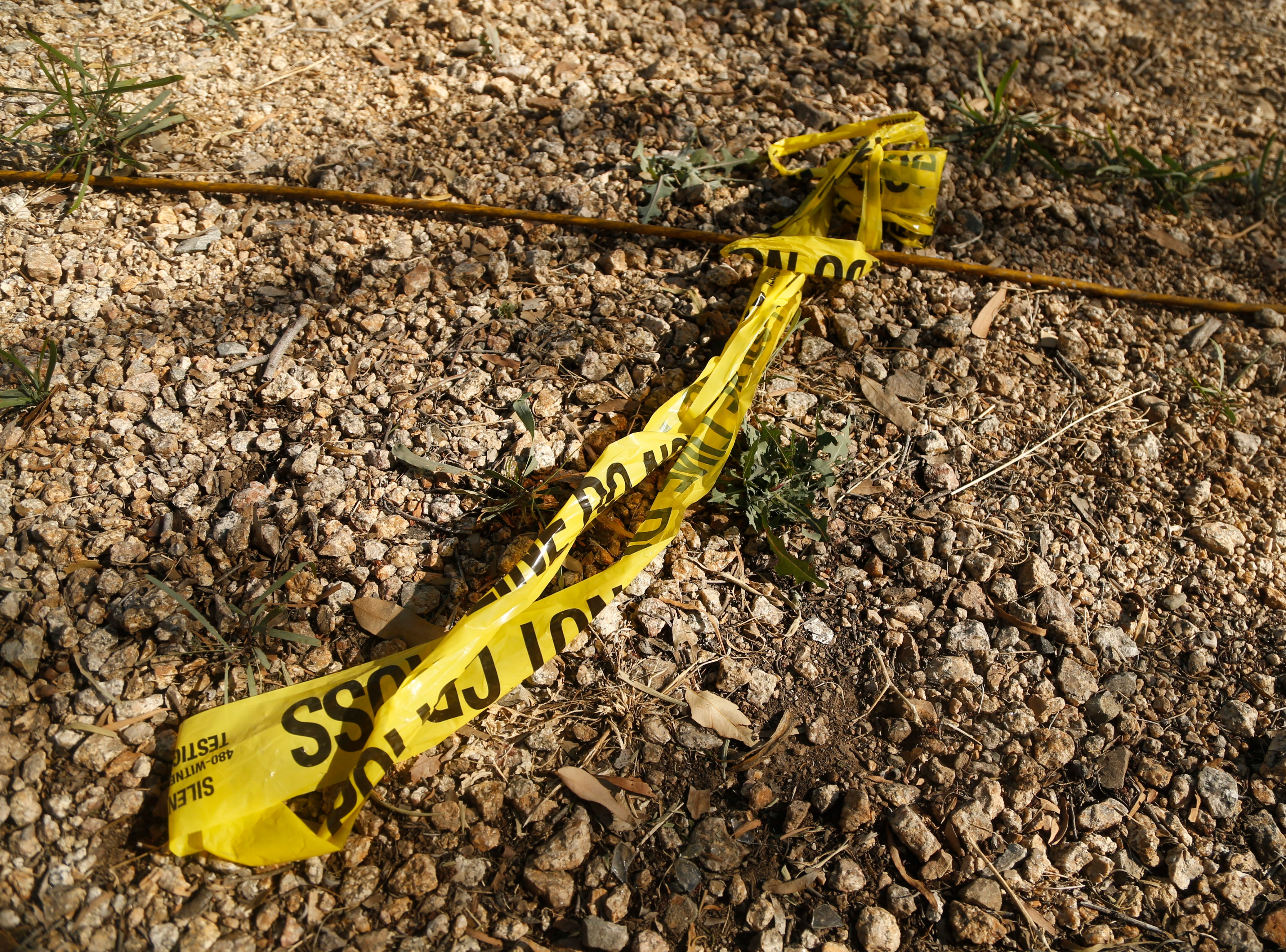 Police tape on the ground near the scene where a 10-year-old girl was shot and killed after an unexpected incident possibly involving road rage in Phoenix, Ariz., on April 3, 2019.