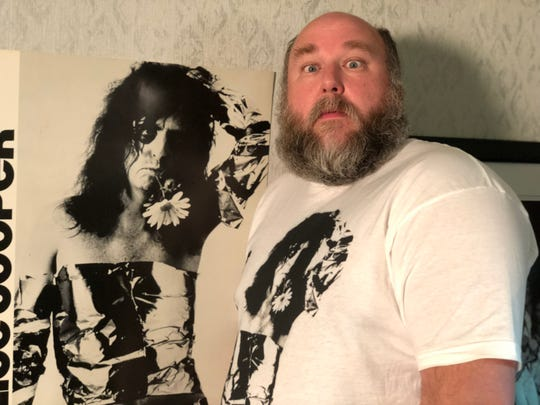 Good Records owner Chris Penn with vintage Alice Cooper poster