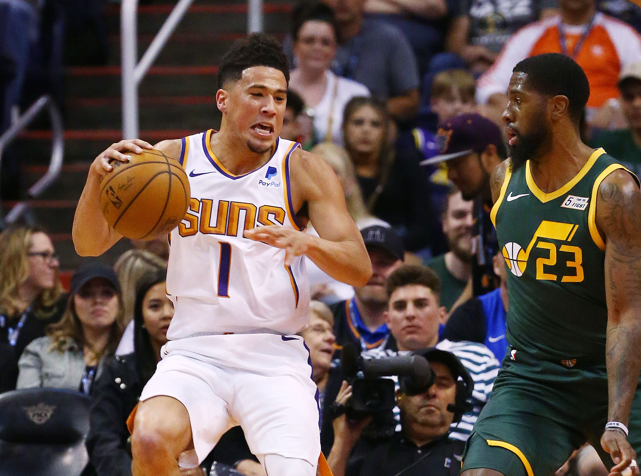 Phoenix Suns guard Devin Booker (1) rolls his left ankle after landing on the foot of Utah Jazz forward Royce O'Neale (23) in the first half on Apr. 3, 2019 at Talking Stick Resort Arena in Phoenix, Ariz. Devin Booker helped off the court to the locker room.