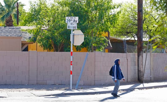A pedestrian walks past the intersection near where a 10-year-old girl was shot and killed after an unexpected incident possibly involving road rage in Phoenix, Ariz., on April 3, 2019.