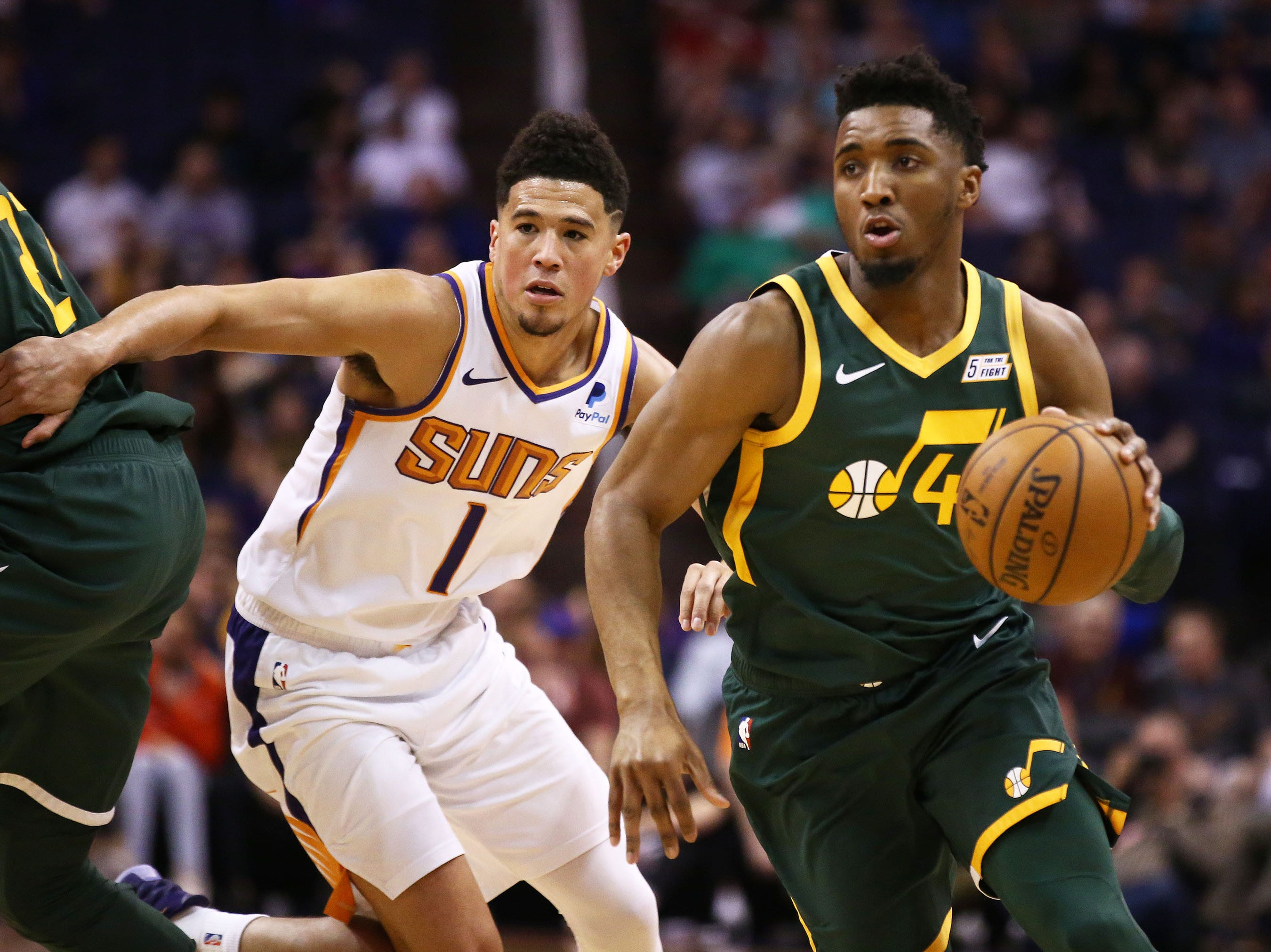 Utah Jazz guard Donovan Mitchell (45) drives past Phoenix Suns guard Devin Booker (1) in the first half on Apr. 3, 2019 at Talking Stick Resort Arena in Phoenix, Ariz.