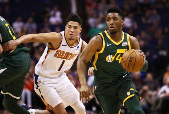 Utah Jazz guard Donovan Mitchell (45) drives past Phoenix Suns guard Devin Booker (1) in the first half on Apr. 3, 2019 at Talking Stick Resort Arena in Phoenix, Ariz.