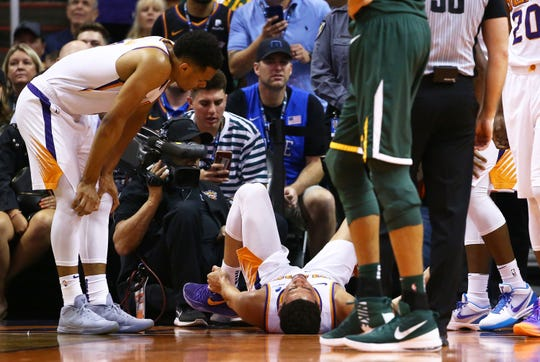 Devin Booker suffers an ankle injury during a game against the Jazz on April 3 at Talking Stick Resort Arena.