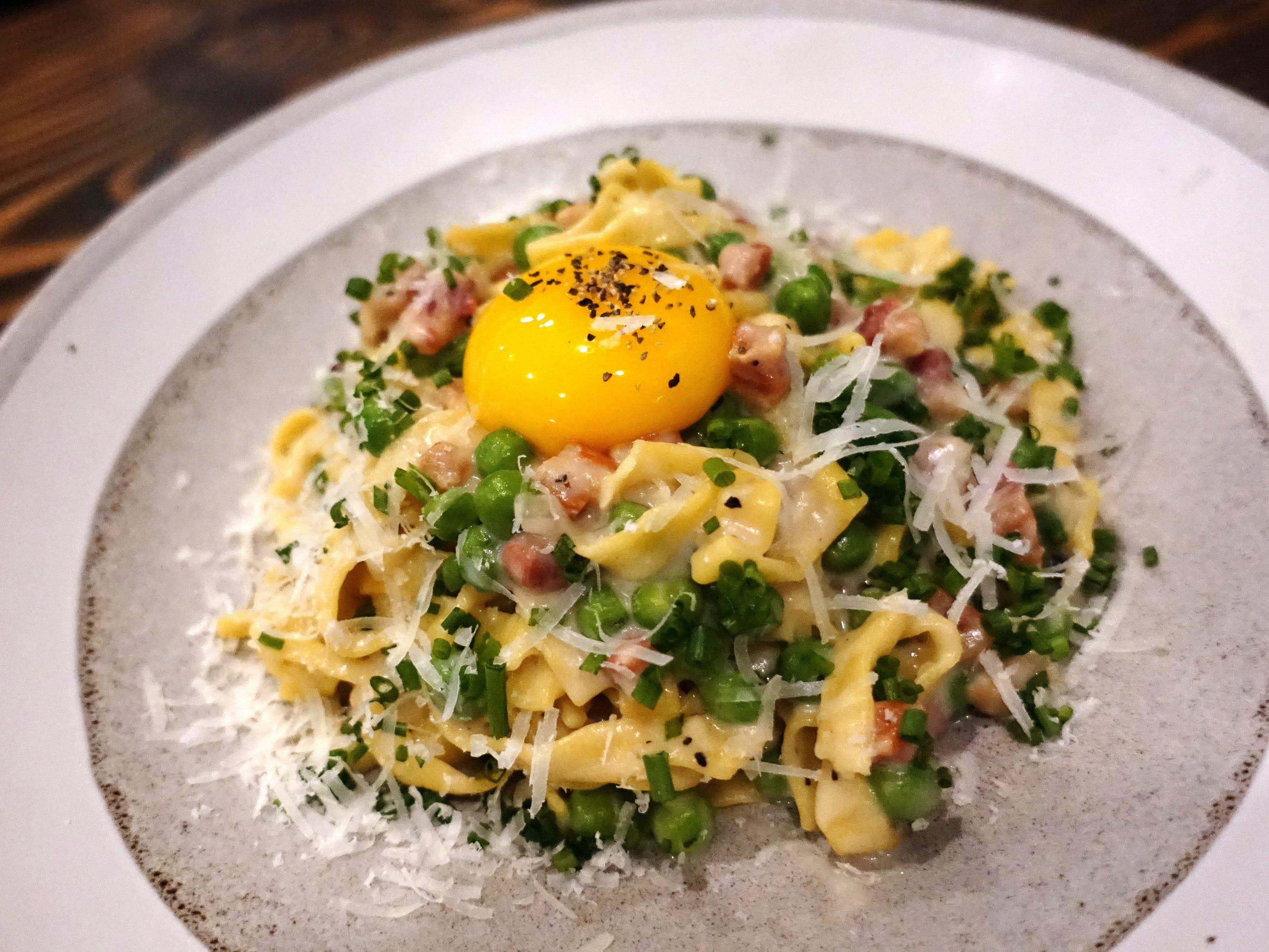 Pasta carbonara with egg yolk, pancetta, pecorino, pepper and peas at Hidden Kitchen in Phoenix.