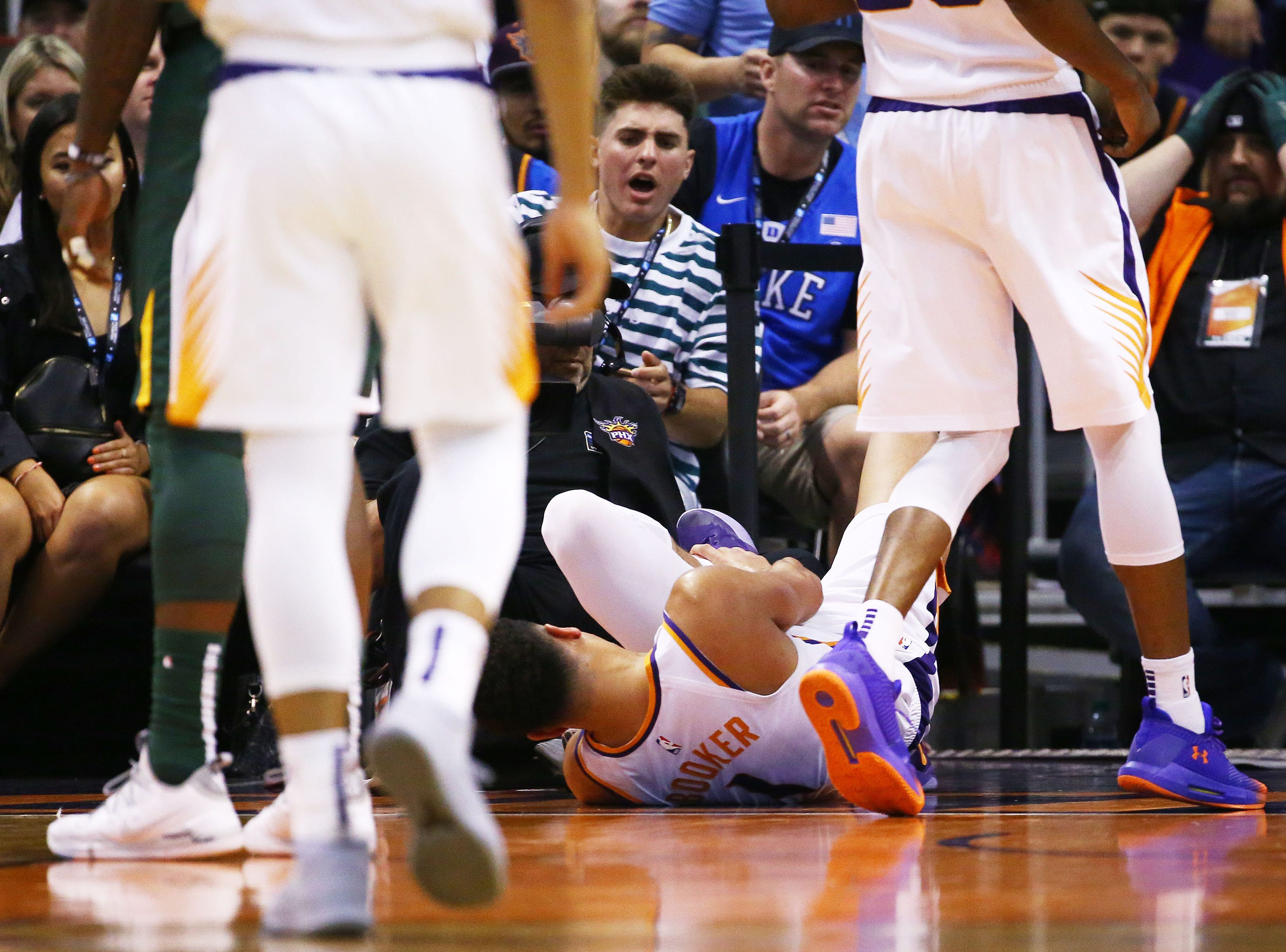 Phoenix Suns guard Devin Booker (1) lays on the court after rolling his left ankle against the Utah Jazz in the first half on Apr. 3, 2019 at Talking Stick Resort Arena in Phoenix, Ariz. Devin Booker helped off the court to the locker room.