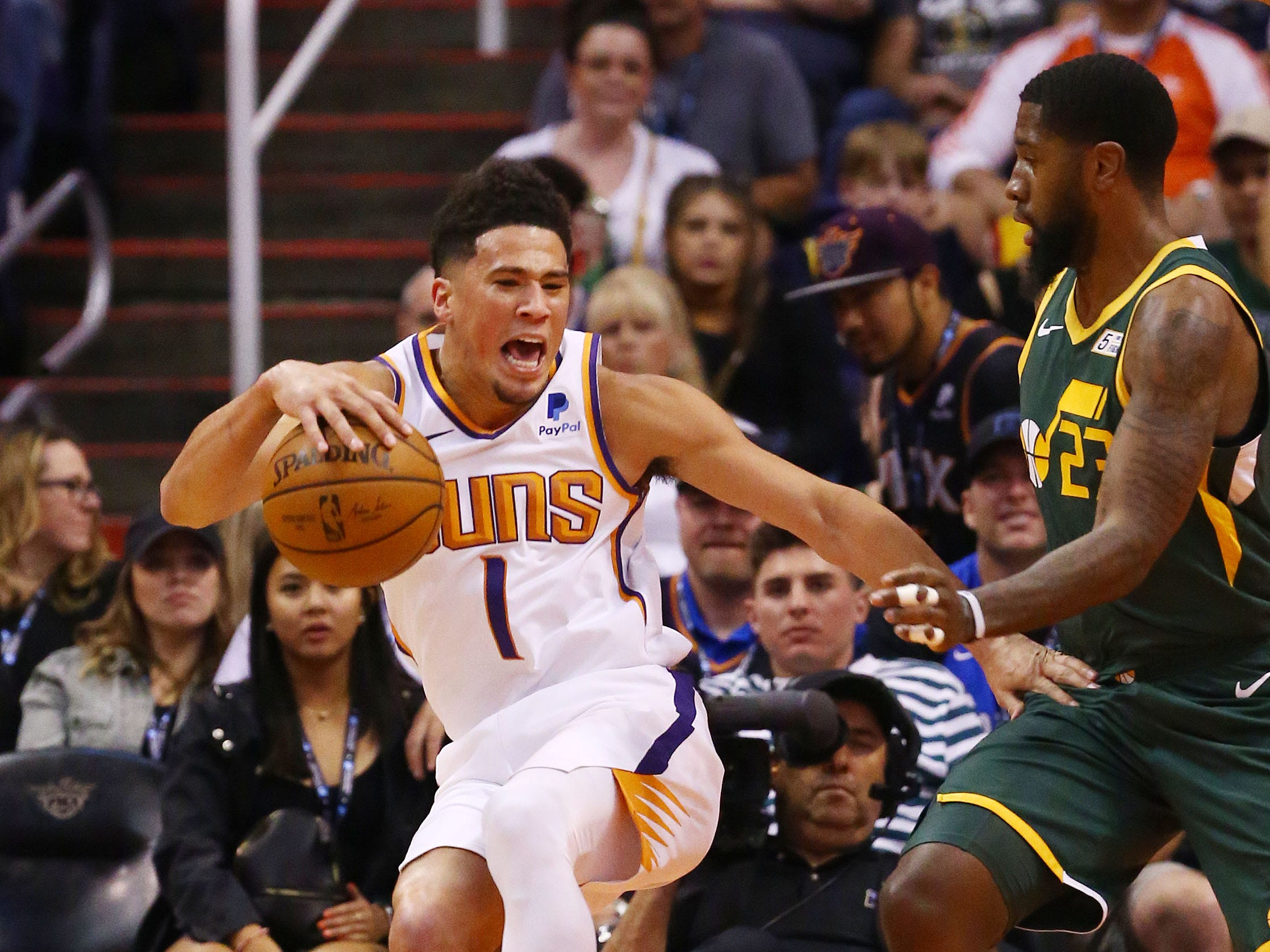 Phoenix Suns guard Devin Booker (1) reacts after rolling his left ankle while landing on the foot of Utah Jazz forward Royce O'Neale (23) in the first half on Apr. 3, 2019 at Talking Stick Resort Arena in Phoenix, Ariz. Devin Booker helped off the court to the locker room.