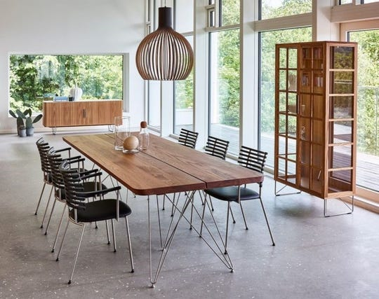 The Plank de Luxe dining table by Naver of Denmark features a rich oiled walnut tabletop and an artistic stainless steel base.  Also pictured are Tiger chairs and China cabinet.