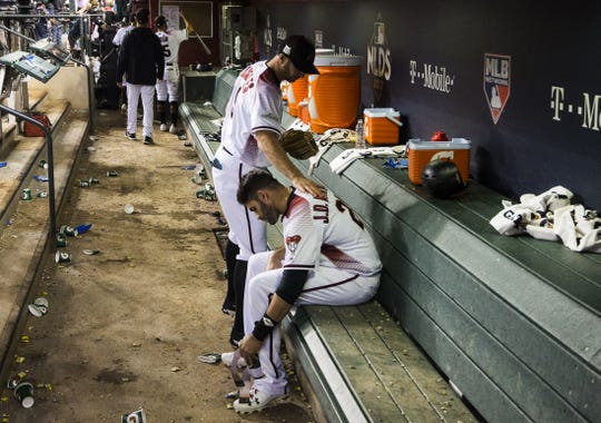 J.D. Martinez sits in the Diamondbacks' dugout after the Dodgers completed a sweep of Arizona in a National League division series.