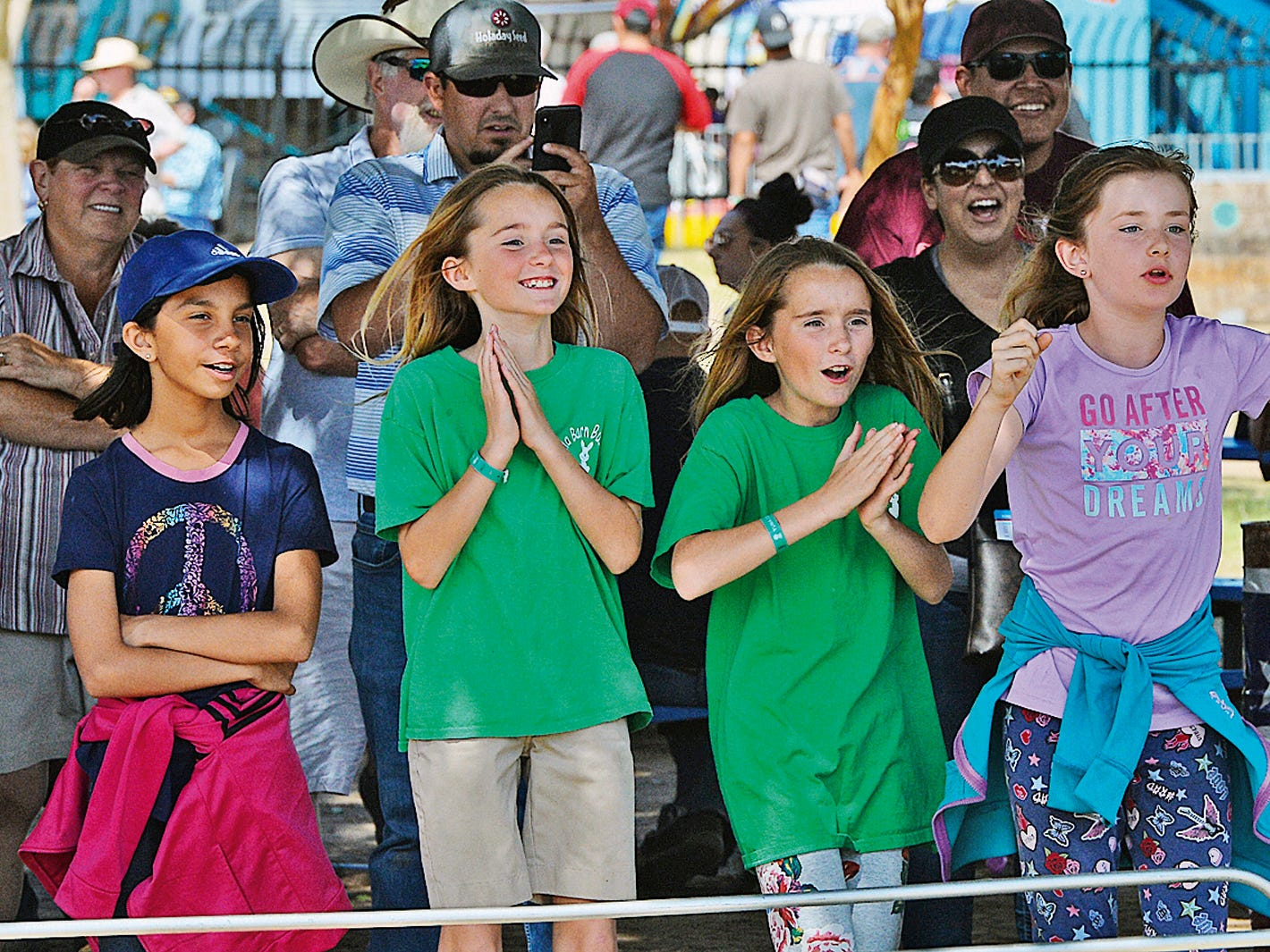 """Racing fans at """"Pork Chop International Speedway"""" cheer for their pig during a Swifty Swine Racing Pigs heat race, Wednesday, April 3, 2019, at the annual Yuma County Fair, in Yuma, Ariz."""