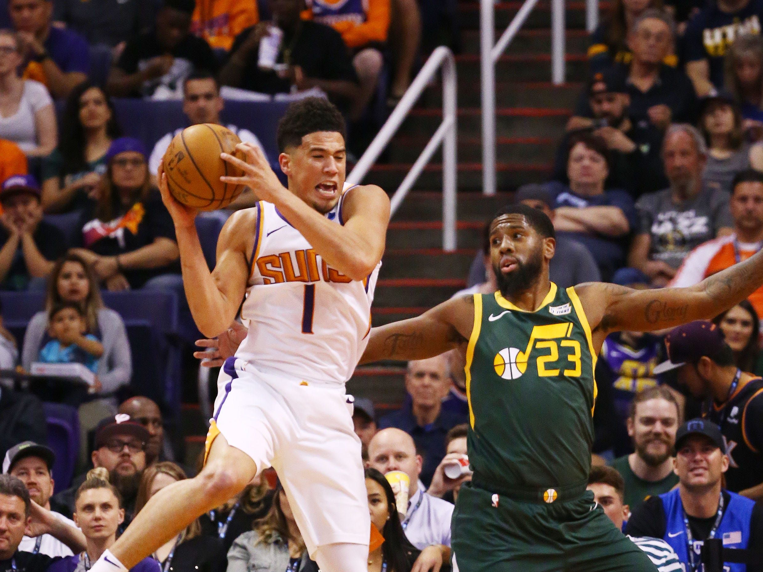 Phoenix Suns guard Devin Booker (1) lands on the foot of Utah Jazz forward Royce O'Neale (23) then rolls his ankle in the first half on Apr. 3, 2019 at Talking Stick Resort Arena in Phoenix, Ariz. Devin Booker helped off the court to the locker room.