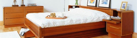 The Scandic bed in classic Danish teak features clean lines and superior functionality, with built-in storage in the headboard and under-bed drawers.