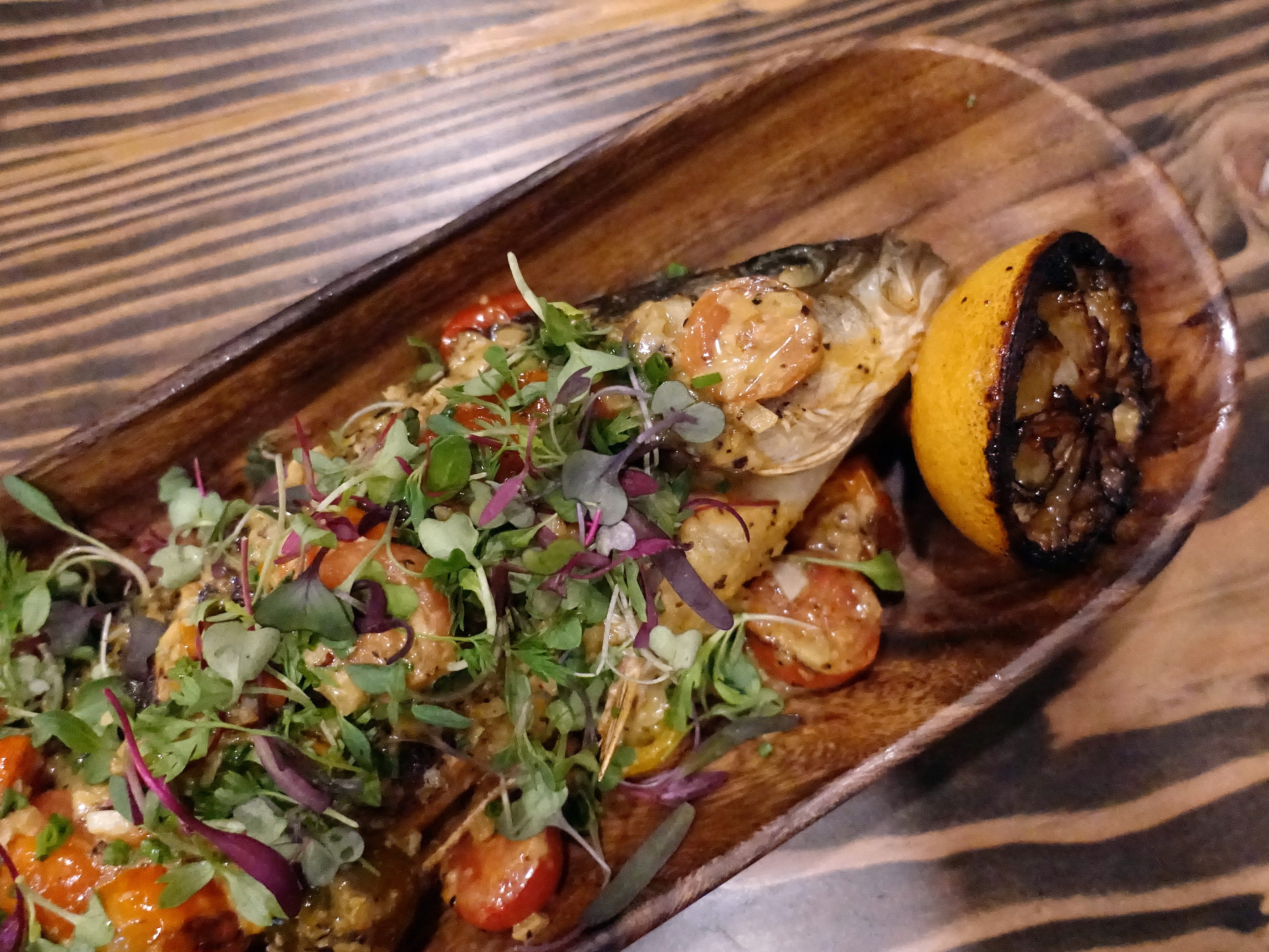 Roasted branzino with tomatoes, white wine, capers, onion and garlic at Hidden Kitchen in Phoenix.
