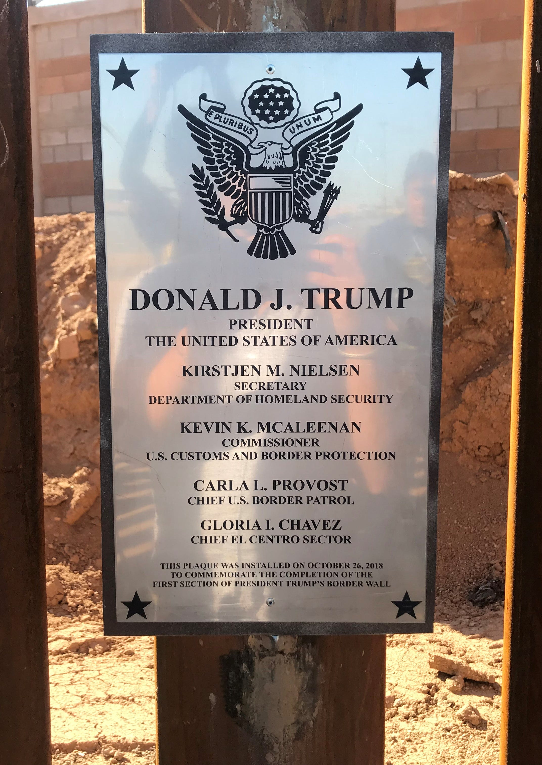 """A plaque marking the """"first section"""" of Trump's border wall rests behind four coils of barbed wire in Calexico, April 3, 2019."""