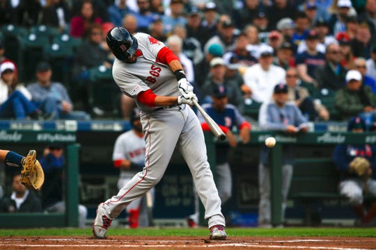 Red Sox designated hitter J.D. Martinez hits an RBI single against the Seattle Mariners during the first inning of a game at T-Mobile Park.