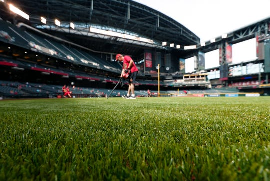 Chase Field grounds crew worker Mike Smothers uses a vacuum to clean up the new artificial turf before a spring training game between the Diamondbacks and Brewers on March 26.