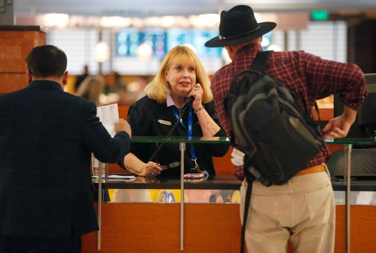 Mary Jo West helps travelers while working at the information desk at Phoenix Shy Harbor Airport on April 3, 2019. The first female news anchor in Arizona has been a volunteer at Terminal 4 for three months.
