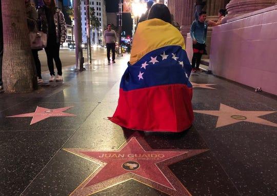 Una mujer envuelta en una bandera de Venezuela posa junto a la estrella de Juan Guaidó en Hollywood.