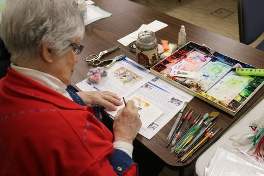 Carol Swope, a regular attendee at the Oak Harbor Public Library's watercolor painting class that meets weekly,  works on a piece Thursday.