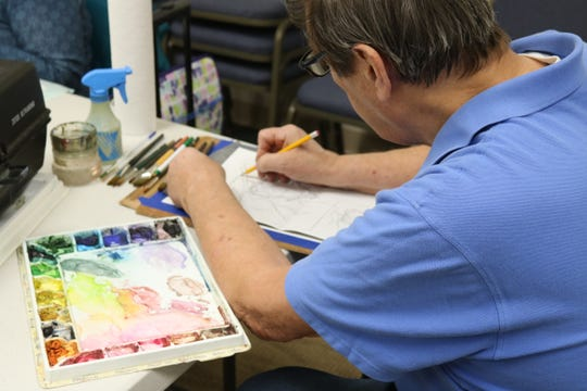 Frank Modliszewski works on an outline prior to painting during Oak Harbor Public Library's watercolor painting class that meets weekly on Thursdays.