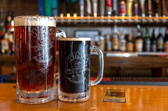 A mug of Black & Blue Brewery's Brown Ale sits on the counter next to a larger mug of Boat Race pale ale on the counter of Wings Etc. in downtown Port Huron.