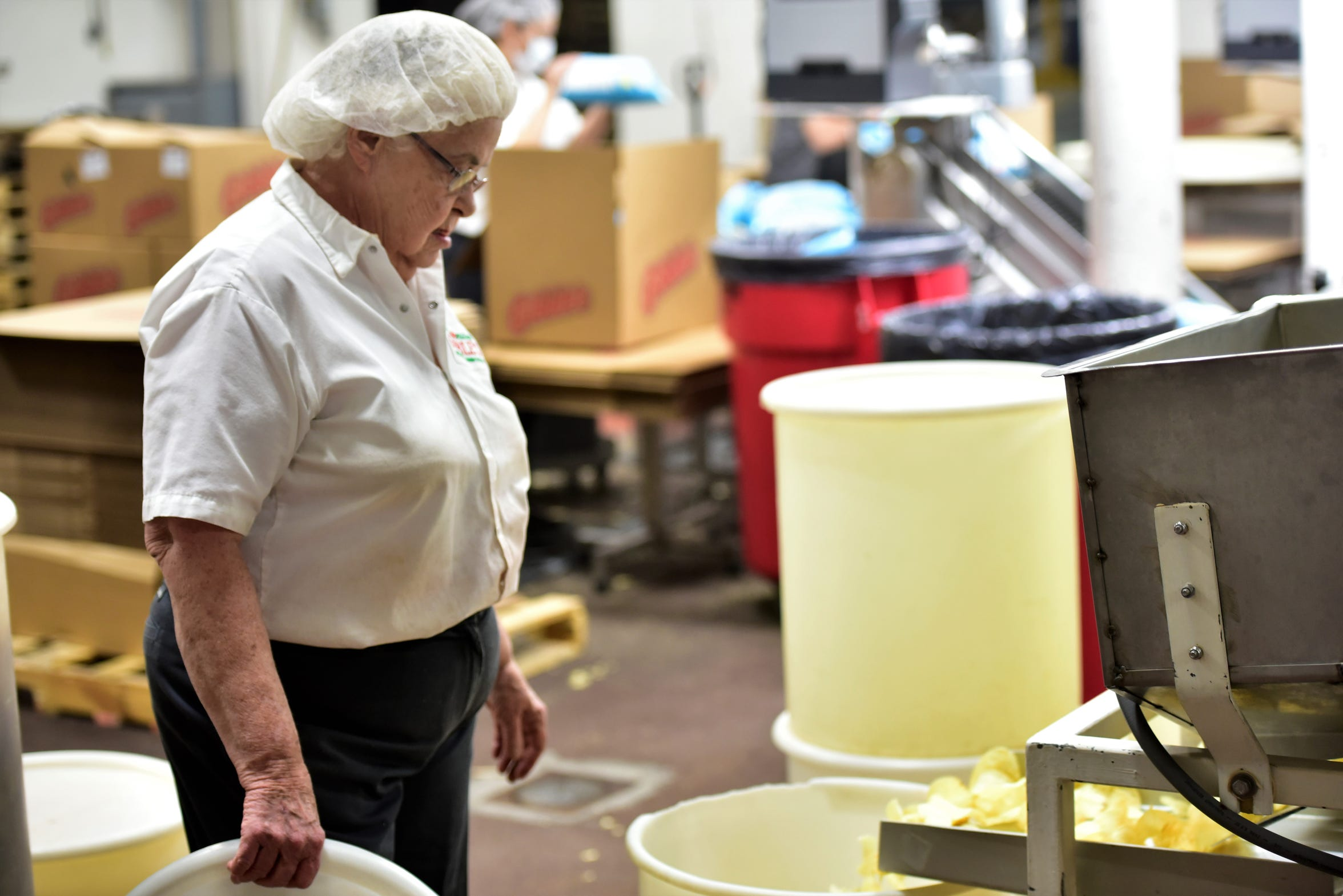 Helen Thomas works at the overflow station as potato chips are made at the Gibble's production facility, 6647 Molly Pitcher Highway, Chambersburg, on March 20, 2019. Thomas, 80, has worked at Gibble's for 41 years.