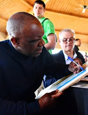 """Baseball Hall of Fame inductee Andre Dawson, left, autographs at the 2019 York Area Sports Night program. The 2020 Sports Night show was not held, as scheduled, on March 19, and the future of the program has been put on """"pause."""" Dawn J. Sagert photo"""