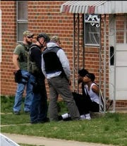 Dion-Taye Jackson, seated, to the left, is arrested by police on Dallas Street Thursday, April 4.