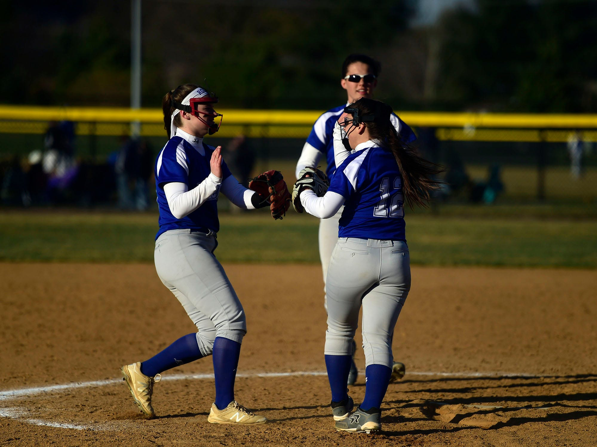 Spring Grove relief pitcher Sara Jones celebrates with third baseman Hannah Gartrell and shortstop Kristen Moore after a strikeout. Jones pitched the final three innings to preserve the win. She struck out six and didn't walk a batter.