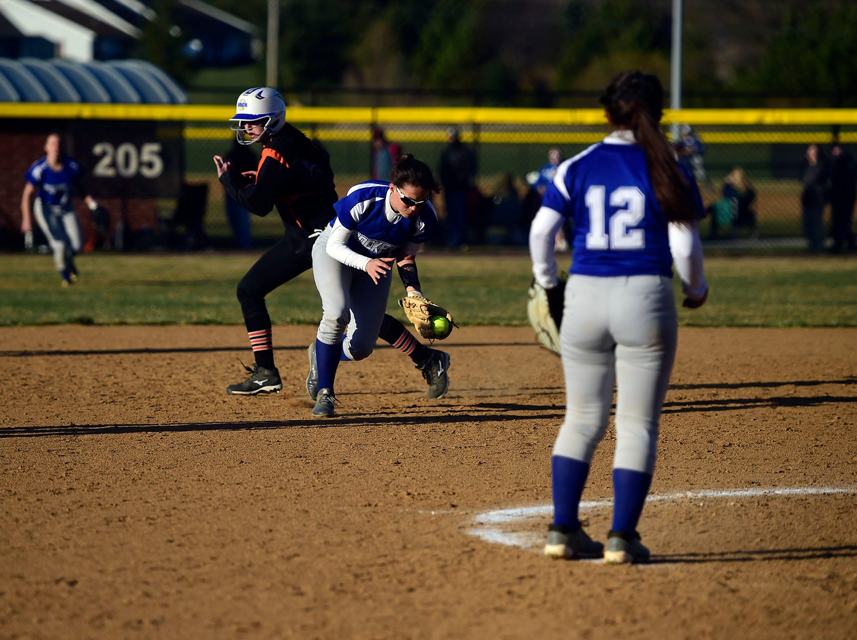 Spring Grove shortstop Kristen Moore scoops up a ground ball in front of a baserunner advancing from second to third base. Moore went 2-for-4 with two runs scored and two RBIs in Spring Grove's 19-14 victory Wednesday, April 3, 2019.