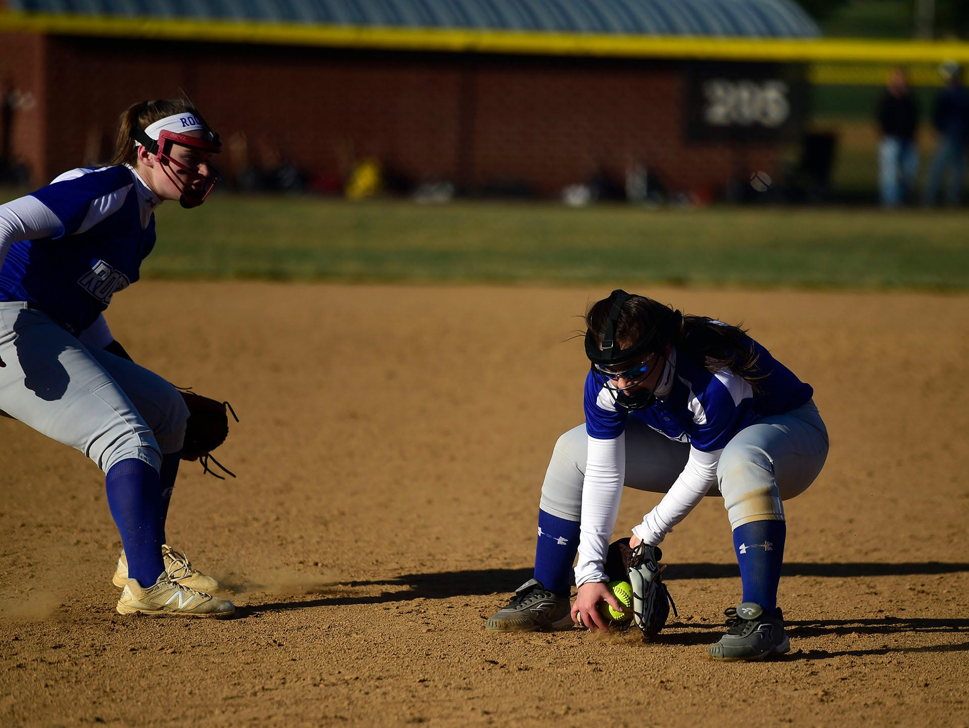 Spring Grove pitcher Sara Jones scoops up the ball in front of third baseman Hannah Gartrell Wednesday, April 3, 2019.