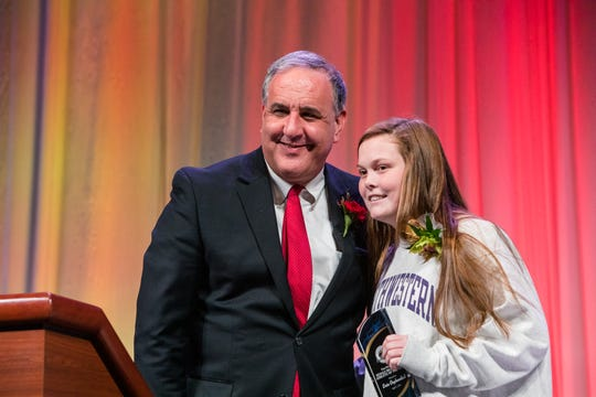 Michael Kilian, executive editor of the Democrat and Chronicle, presents Spencerport's Erin Coykendall with the Democrat and Chronicle's High School Female Athlete of the Year Award at the Rochester Press-Radio Club's Day of Champions Dinner on April 3, 2019.