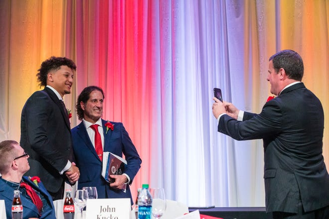 Master of ceremonies John Kucko takes a photo of Charlie Wagner Award winner John Grillo with Patrick Mahomes at the Rochester Press-Radio Club's Day of Champions Dinner on April 3, 2019.