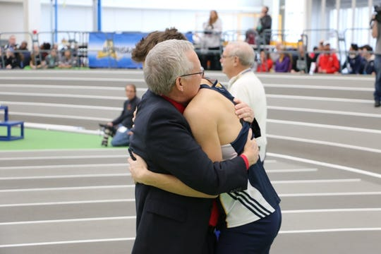 Penfield coach Dave Hennessey, left, hugs Victor's Mike Bayley after Bayley won the state championship in the 55-meter hurdles last month.