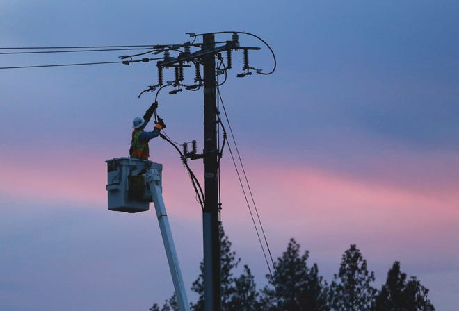 In this Nov. 26, 2018, file photo, a Pacific Gas and Electric lineman works to repair a power line in fire-ravaged Paradise, Calif. PG&E officials said Friday that due to the first red-flag warning of the year, they may turn off power to customers in eight Northern California counties to reduce the risk of wildfire.