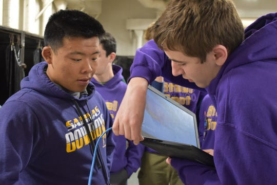 "Thomas An and Michael Montemurno set up to test their ""Steel Boot"" robot at Salinas High School."